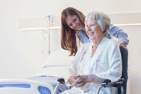 Carer or young daughter wheeling an elderly woman in a wheelchair bending down to smile at her indoors in a hospital room on a ward or old-age home