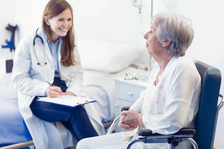 Nurse or doctor writing patient notes in a ward for a smiling elderly woman seated in a wheelchair in a medical and healthcare concept