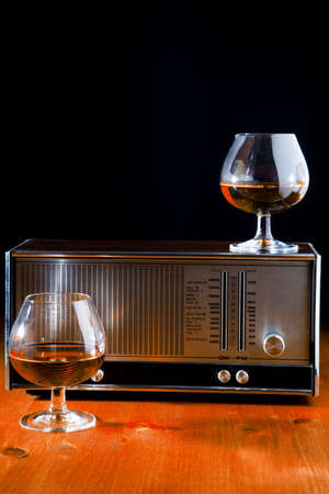 two glasses of brandy and a vintage radio