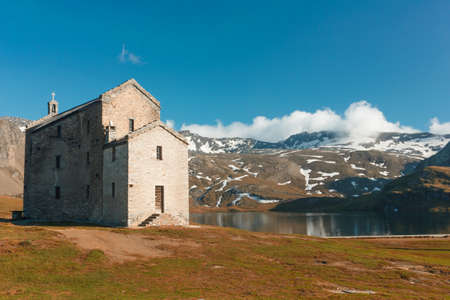 oratoria: Miserin Lake, one of the most enchanting in the Graie Alps. The Notre-Dame des Neiges Sanctuary overlooks the lake and is an ancient oratory that became famous for miracles. Champorcher Aosta Italy Foto de archivo