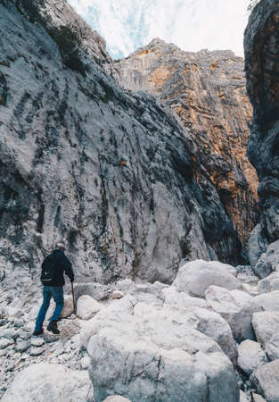 Aged Man hiking insdide the deepest canyon in Europe  - Gola Su Gorroppu. Stock Photo
