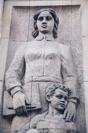 WARSAW, POLAND - March 2018 - A social realist relief of a socialist woman and kid in the center of Polish capital