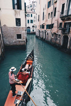Gondolier with gondola through green canal waters of Venice Italy.