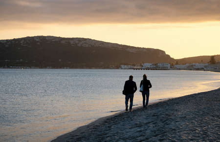 The main beach of Cagliari (poetto sella del diavolo) with two walking lovers at sunset - Sardinia
