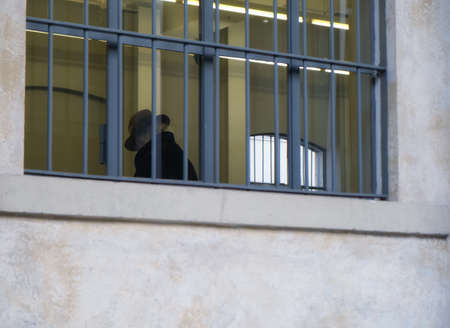 sad old senior man with hat inside building with barred windows - Law and justice concept