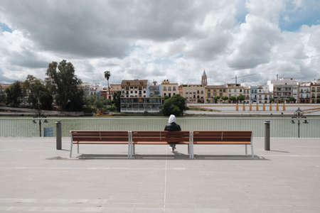 lonely boy sitting on a bench along the river in Seville in a cloudy day - Spain - Imagens