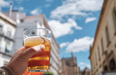 递人拿着一杯bier在一个晴天做欢呼对蓝天 - 这是吐司社会饮用的
