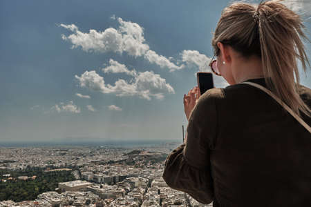 blonde woman or girl with smart-phone taking photo at the city of Athens from the Mount Lycabettus in a sunny day