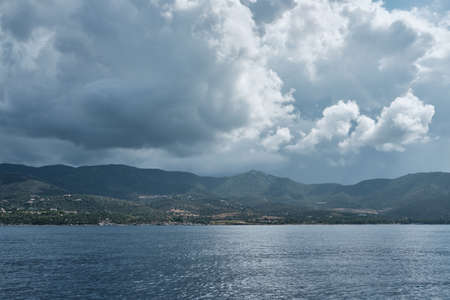 Seascape panorama from little boat in a cloudy day along the shoreline in sardinia Archivio Fotografico