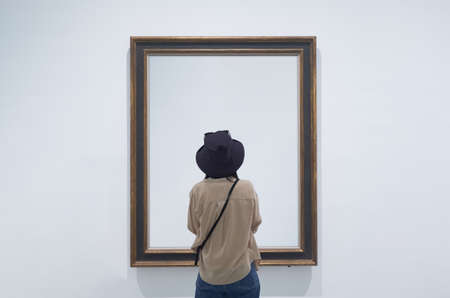 interior view of a lonely girl or tourist looking at blank canvas or painting at a museum or gallery