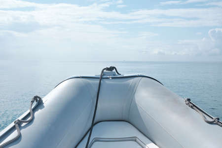 Front view grey Inflatable rubber boat floating on the sea with seascape horizon in a sunny day - body copy