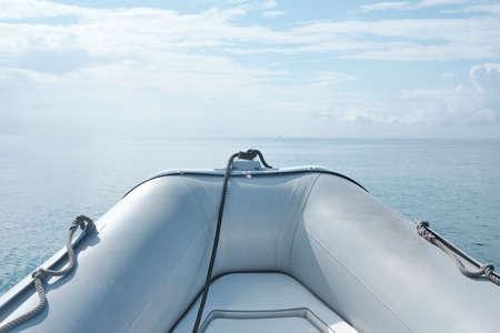 Vista frontal bote de goma inflable gris flotando en el mar con horizonte marino en un día soleado - body copy