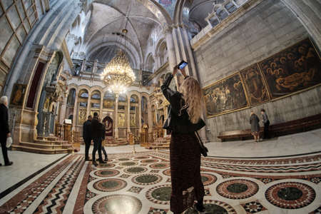 DEC 2019 Girl taking photo with smart phone in the Church of the Holy Sepulcher - Stone of Unction in Jerusalem, Israel Reklamní fotografie