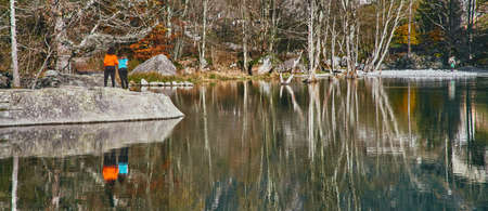 panorama view of small lake with reflections and multicolor woods, in autumn season lake in Val di Mello, Val Masino, Italy - lombardy