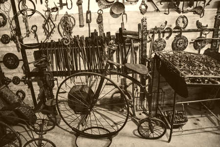 old bicycle and iron tools hanging on the wall - hardware workshop