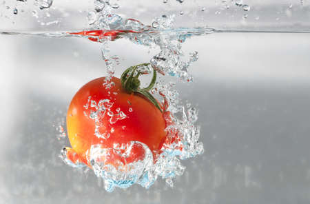 A cherry tomatoe dip into water Stock Photo - 18191139