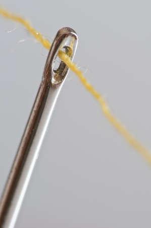 resourceful: yellow cotton thread through a needle eye