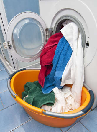 Open Washing machine with white, green, red and blue cloths Stock Photo - 18229168