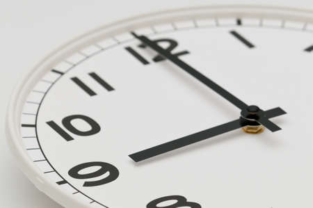 White clock with black hands showing nine oclock Stock Photo