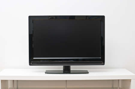 Black flat screen tv set on white table and wall photo