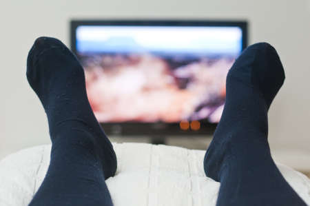 Laying in bed and watching tv in dark socks Stock Photo
