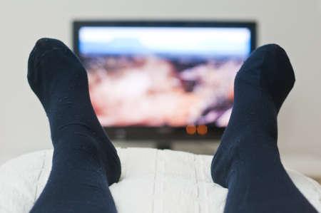 lazy: Tv Acostado en la cama y mirando en calcetines oscuros