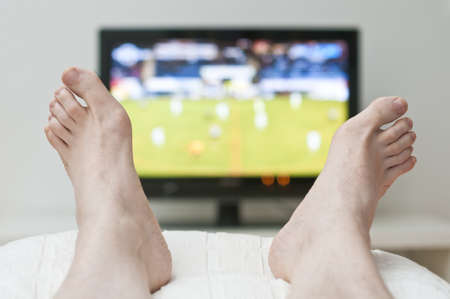 bare feet toes: Laying in bed and watching tv between bare feet