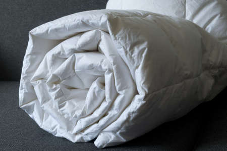 Detail of a rolled white down comforter