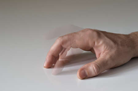 Hand on table with anxious tapping finger