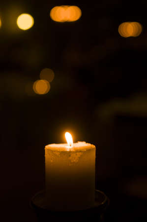 Holiday candle with blurred lights in background Stock Photo