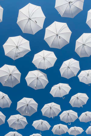 air diffuser: Ornamental white umbrellas flying in the blue sky Stock Photo