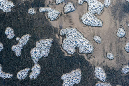 induced: Colorful foam and bubbles induced by pollution in sea water on  beach
