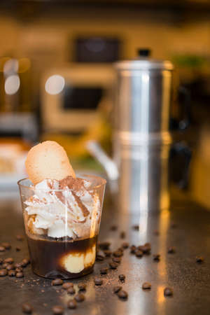 Artisan preparation of a glass cup of Italian ice cream gelato affogato, drowned, in espresso coffe with whipped cream and cats tongue cookies.
