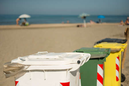 Color coded bins on beach to separate and recycle plastic, paper, metal and organic garbage.