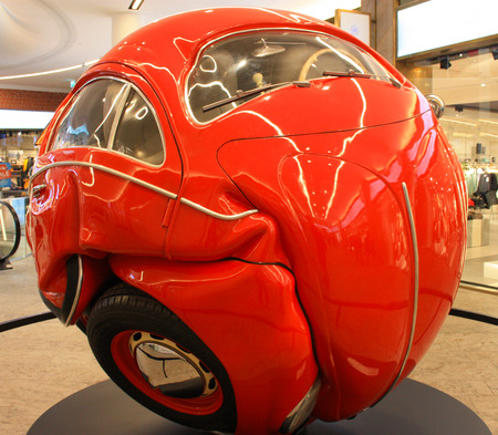 red car curled up on itself to form a round ball Banco de Imagens