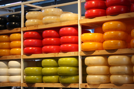 many different shapes of colored Dutch cheese stacked on neat shelves. culinary product typical of amsterdam