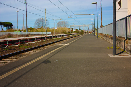 a small deserted local station during the day. sidewalk for waiting passengers waiting for trains for their journeys, between departures and arrivals