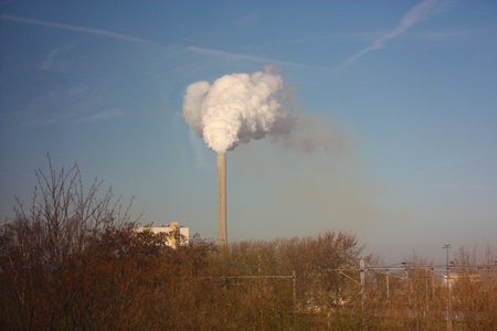 outlet of a chimney that dumps the remains of industrial processing into the clear blue sky, polluting our beautiful planet