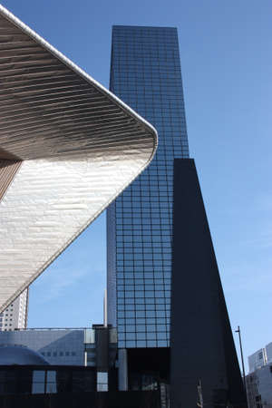 A trip to Holland on a beautiful sunny day. Walk in the square of Rotterdam Central Station admiring the blue sky and geometric constructions and tall buildings