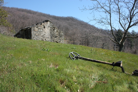 a metal detector resting on a lawn, lying on a very green clearing, a field of the Apuan Alps in Tuscany. in front of an abandoned ruin, once a house for farmers and cattle ranchers in the mountains Фото со стока