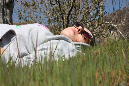 Caucasian girl lying on a large green field, a spring meadow. person wearing jeans and a gray sweatshirt. dozing peacefully taking a relaxing break Stock Photo