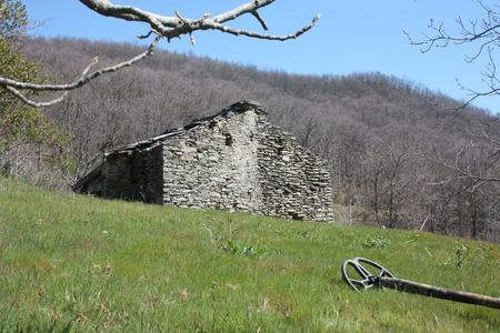 a metal detector resting on a lawn, lying on a very green clearing, a field of the Apuan Alps in Tuscany. in front of an abandoned ruin, once a house for farmers and cattle ranchers in the mountains Stock Photo