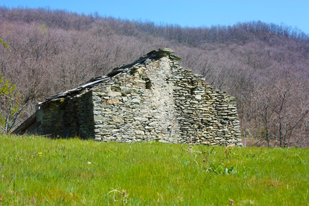 ruin destroyed. an old house built of stones abandoned in a green clearing, in the middle of the nature of the park of the Apuan Alps, Tuscan Apennines in Italy Banco de Imagens