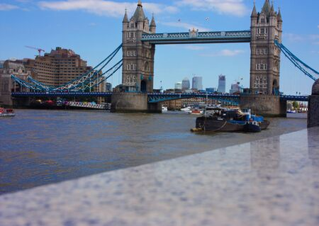 The famous London Bridge on a blue sky summer day. The tranquil water of the Thames river in the UK