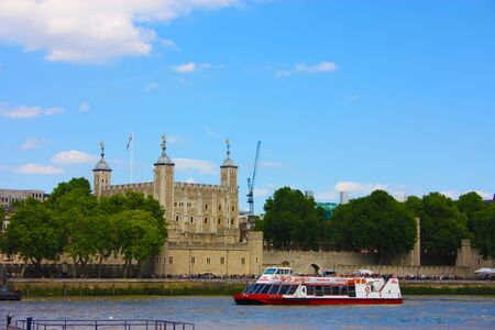 A tourist ferry transports tourists along the Thames river between the buildings and historic buildings of London in Uk