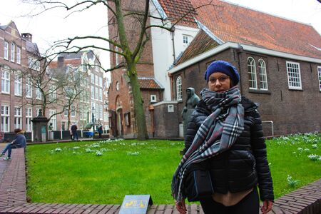 Caucasian tourist girl on field trip in the secret garden of the Beguines in Amsterdam on a winter cloudy day Banco de Imagens