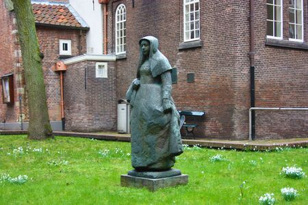 The quarter of the Beguines of Amstedam. Beguinage in the secret garden of the Beguines in Amsterdam on a winter cloudy day
