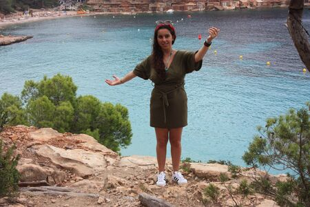 caucasian girl on the cliff of cala saladeta enjoys summer vacation in the wild nature of the balearic islands enjoying in ibiza