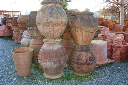 open air workshop of ceramics, earthenware, orange and brown terracotta flower pots craftmanship in tuscany Stock Photo