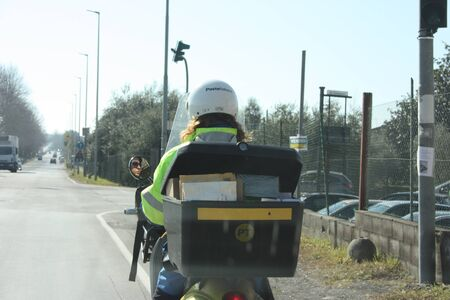 postman at work on her scooter in the cold doing her job in delivering mail to citizens for public service on the streets of a city in the middle of traffic in italy